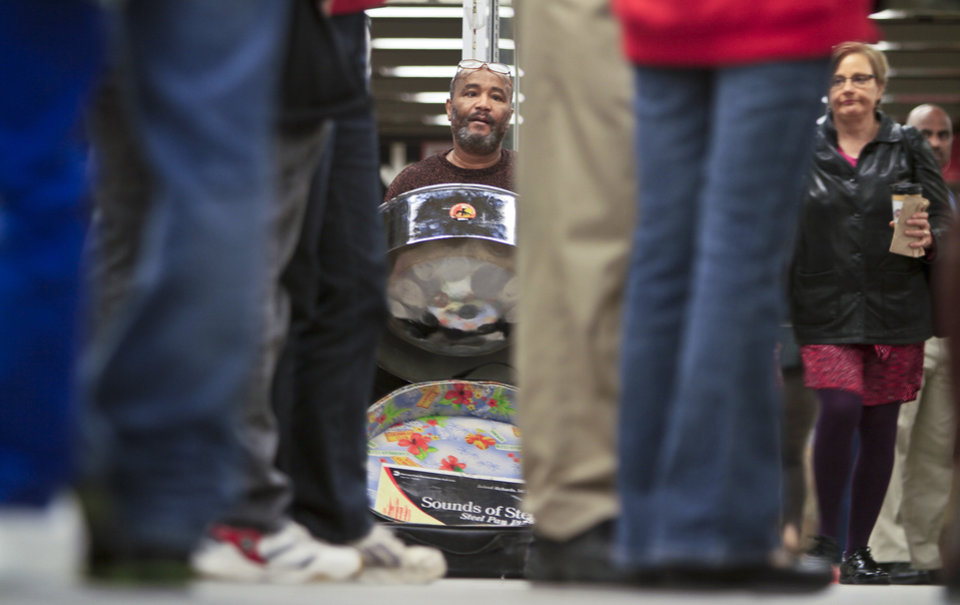 Photo - In this Wednesday, Oct. 9, 2013, photo, Roland Richards, center, plays a steel drum on the 34th Street subway platform, in New York. Richards, who immigrated from Trinidad and brought the indigenous pan music as well, says he is a professional welder by trade.