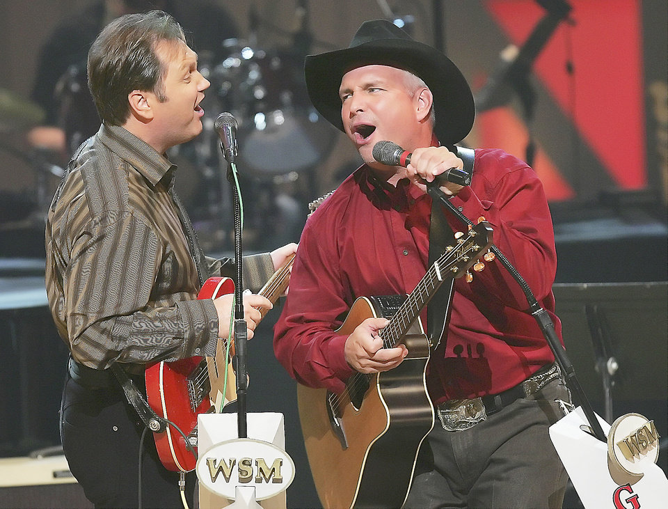 "Steve Wariner, left, sings ""Long Neck Bottle"" with Oklahoma star Garth Brooks on stage of the Grand Ole Opry in 2005 during its 80th birthday celebration in Nashville, Tenn. AP File Photo"