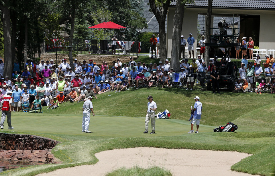 Photo - Gene Sauers, second from left, and Bernhard Langer, second from right, look over the fourth green during the third round of play at the 2014 U.S. Senior Open golf tournament at Oak Tree National in Edmond, Okla., Saturday, July 12, 2014. (AP Photo/Sue Ogrocki)