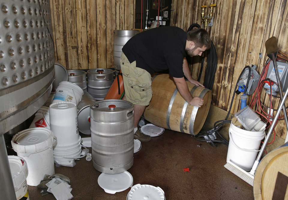 Photo - Tyler Dahl looks over a $16,000 barrel of Pinot Noir wine that fell from a rack and broke open after an earthquake at Dahl Vineyards Sunday, Aug. 24, 2014, in Yountville, Calif. A large earthquake caused significant damage and left at least three critically injured in California's northern Bay Area early Sunday, igniting fires, sending at least 87 people to a hospital, knocking out power to tens of thousands and sending residents running out of their homes in the darkness. (AP Photo/Eric Risberg)