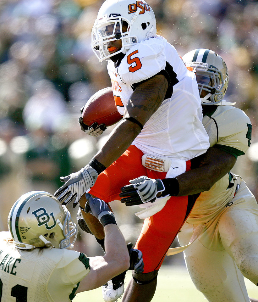 Photo - OSU's Keith Toston (5) is brought down by Baylor's Jordan Lake (21) , left, and Antonio Jones (6) during the college football game between Baylor University and Oklahoma State University (OSU) at Floyd Casey Stadium in Waco, Texas, Saturday, Oct. 24, 2009.  Photo by Sarah Phipps, The Oklahoman