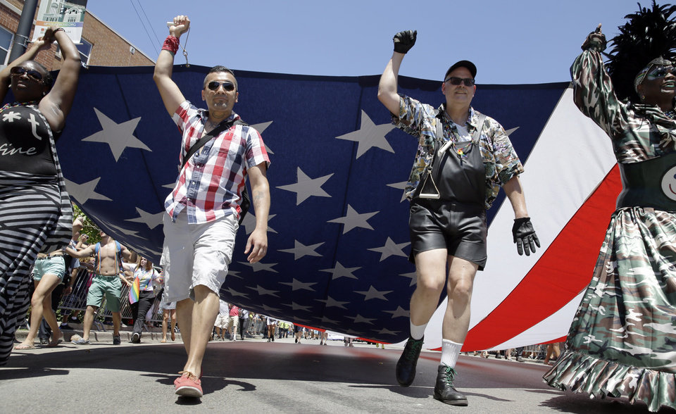 Photo - Members of the Gay, Lesbian and Bisexual Veterans Association march with a big U.S. Flag at the 45th Annual Chicago Pride Parade during the parade on Broadway  in Chicago, Sunday, June 29, 2014. The event, the first since Illinois' law allowing same-sex marriage went into effect, has 200 registered entrants, with about 1 million expected to participate. (AP Photo/Nam Y. Huh)