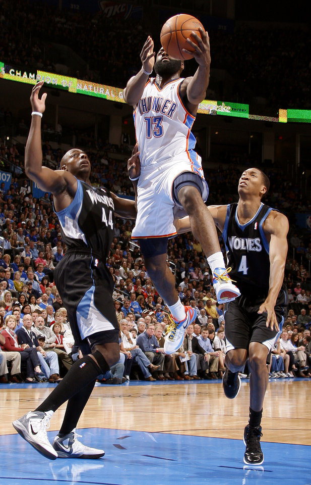 Photo - Oklahoma City's James Harden (13) goes to the basket between Minnesota's Anthony Tolliver (44) and Wesley Johnson (4) during the NBA basketball game between the Oklahoma City Thunder and the Minnesota Timberwolves at Chesapeake Energy Arena in Oklahoma City, Friday, March 23, 2012. Photo by Bryan Terry, The Oklahoman