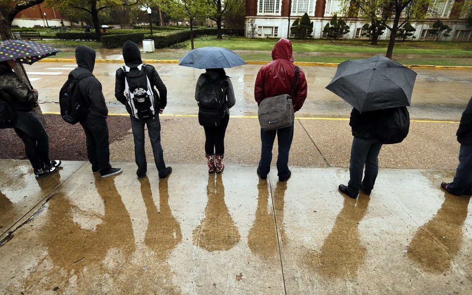 Students wait in the rain for a bus at the University of Oklahoma (OU) on Wednesday, April 10, 2013 in Norman, Okla.  Photo by Steve Sisney, The Oklahoman
