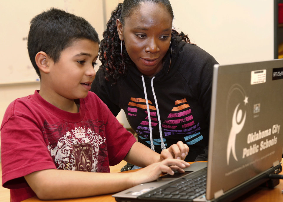 University of Central Oklahoma student Jakky Finley helps Linwood Elementary School  third-grader Patrick Goolsby with his reading using a laptop computer.    Photo by Jim Beckel, The Oklahoman <strong>Jim Beckel - THE OKLAHOMAN</strong>