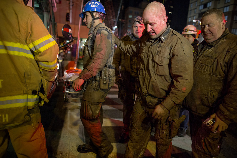 Photo - Officers of the New York City police Emergency Services Unit, covered in mud and dirt, walk to a waiting bus to warm up after securing the rescue of a construction worker trapped underground at an MTA subway construction project in New York early Wednesday, March 20, 2013. The worker, trapped for several hours, was lifted from underground with the assistance of the New York police and fire departments. Fire officials say he is awake and conscious and is being evaluated at a local hospital. (AP Photo/Craig Ruttle)