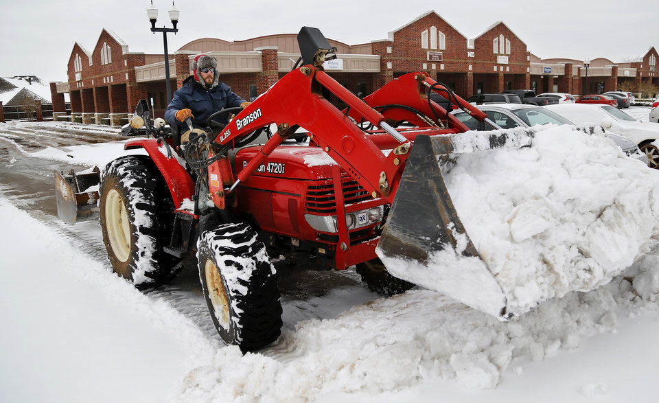 Photo - Clint Stealey operates a tractor with a scoop attached to the front to remove snow from the parking lot of Woodlands Office Park in Midwest City  on Friday,  Dec. 6, 2013. Stealey owns a lawn care business and he teamed with  JayParsons, owner of a dozer company, to clear parking lots for businesses when it snows. Stealey wears a hat lined with rabbit fur that was brought to him by a family member in Colorado. Photo by Jim Beckel, The Oklahoman