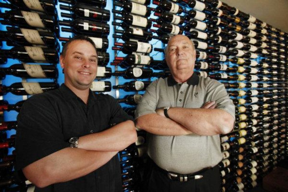 RESTAURANT: Billy Wilson, left and his dad Bill Wilson stand with the wine selection at Opus Prime Steakhouse in Oklahoma City, Oklahoma , Thursday, June 3, 2011. Photo by Steve Gooch ORG XMIT: KOD <strong>Steve Gooch - THE OKLAHOMAN</strong>