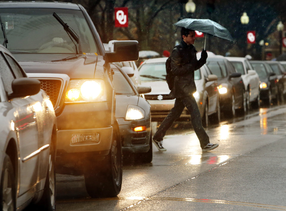 Photo - Traffic backs up on Lindsey Street as students head to class in the rain on the campus of the University of Oklahoma (OU) on Tuesday, Feb. 12, 2013 in Norman, Okla.  Photo by Steve Sisney, The Oklahoman