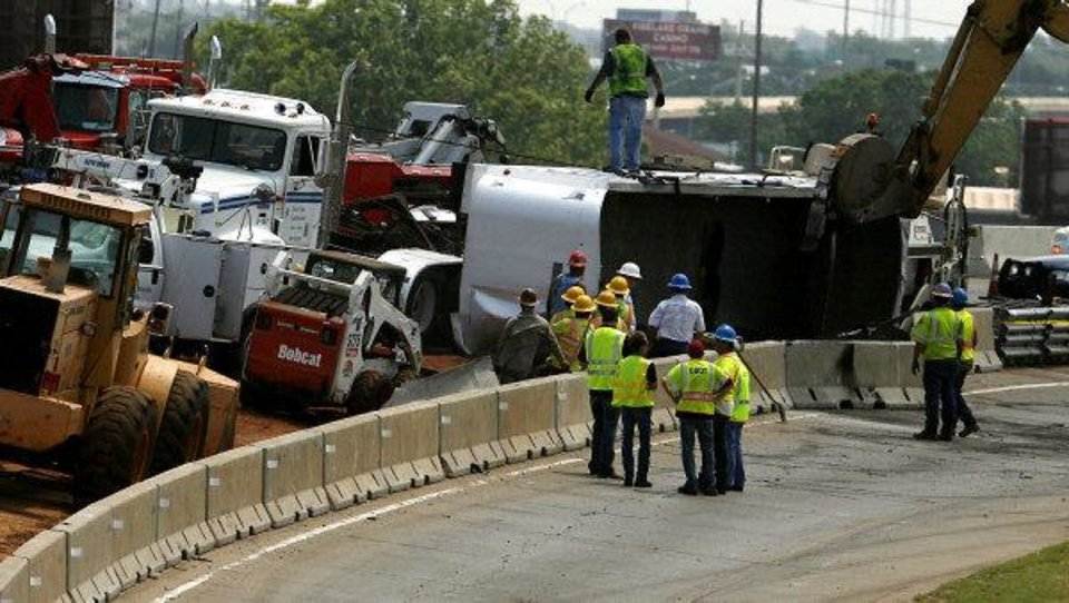Photo - Emergency crews work to clean up after a Monday accident on northbound Interstate 35 north near the Interstate 235 ramp near downtown Oklahoma City. One person was trapped after a semi-trailer rig hauling asphalt overturned. The victim was freed by emergency responders and taken to a hospital. Photo by Ashley R. West, The Oklahoman ORG XMIT: KOD  Ashley R. West - Ashley R. West