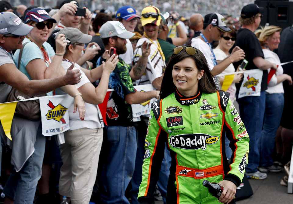 Danica Patrick smiles as she walks past fans during driver introductions before the NASCAR Sprint Cup Series auto race, Sunday, March 3, 2013, in Avondale, Ariz. (AP Photo/Ross D. Franklin)