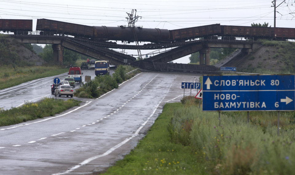 Photo - Cars queue to drive under a destroyed railroad bridge over a main road leading into the east Ukraine city of Donetsk, near the village of Novobakhmutivka, 20 km North from the city of Donetsk, eastern Ukraine Monday, July 7, 2014. The bridge has been destroyed, blocking a key access route to the rebel-held city. (AP Photo/Dmitry Lovetsky)