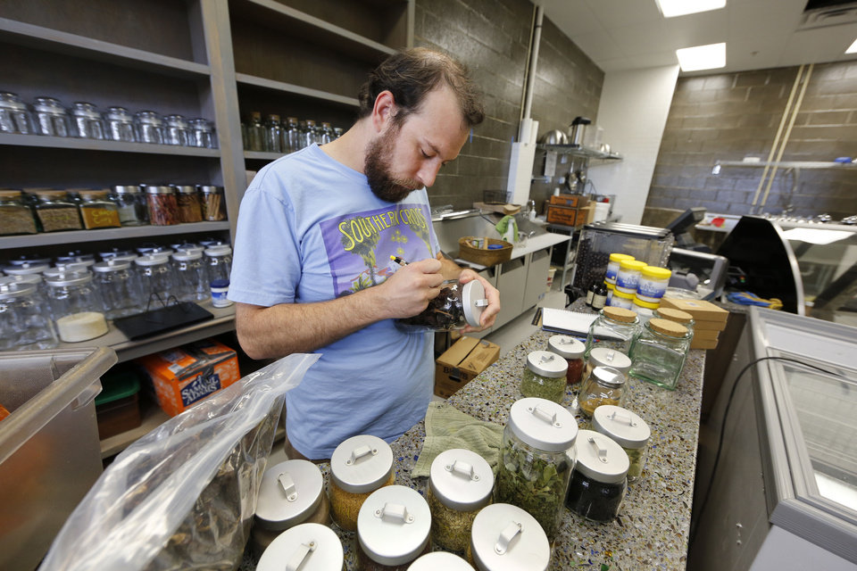 Photo - Doug Rader labels containers at the Spice Bar at Native Roots Market at NE 2 and Walnut in Oklahoma City. Photo by Steve Gooch, The Oklahoman  Steve Gooch - The Oklahoman