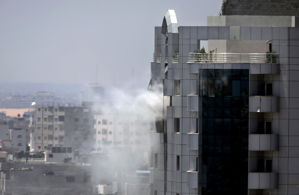 Photo - Smoke rises from a building was hit with an Israeli strike in Gaza City, Tuesday, July 29, 2014. Israel struck symbols of Hamas' control of Gaza and the strip's only power plant on Tuesday, escalating its military campaign against the Islamic militant group with the heaviest bombardment in the fighting so far.(AP Photo/Khalil Hamra)