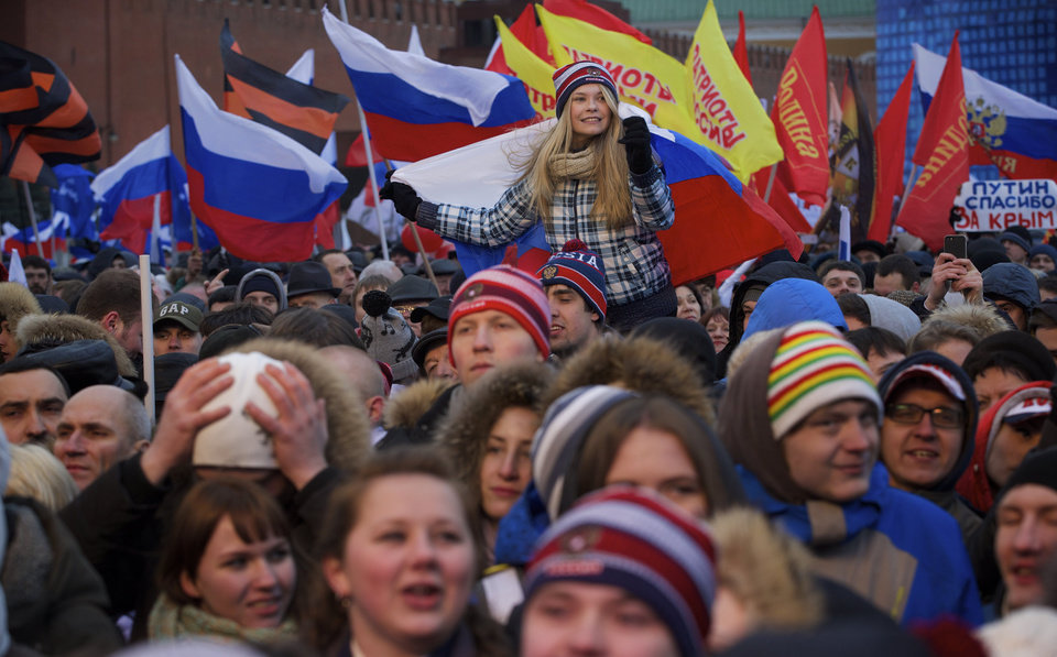 Photo - Participants in a rally in support of Crimea joining Russia, hold Russian flags in Red Square in Moscow, Tuesday, March 18, 2014. With a sweep of his pen, President Vladimir Putin added Crimea to the map of Russia on Tuesday, describing the move as correcting past injustice and responding to what he called Western encroachment upon Russia's vital interests. (AP Photo/Pavel Golovkin)