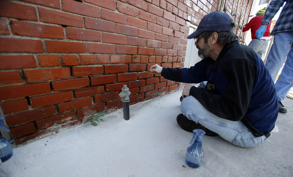 Lloyd Bumm prepares a wall for new mortar as Bob Yapp teaches residents how to make masonry repairs on a downtown building on Saturday, Nov. 17, 2012 in Norman, Okla.  Yapp is a nationally recognized historic preservation expert who is leading a workshop on masonry repair.  Photo by Steve Sisney, The Oklahoman
