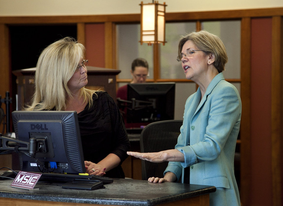 Photo -   Democratic candidate for the U.S. Senate Elizabeth Warren, right, speaks with Financial Services Representative Merri Gagne, of Quincy, Mass., left, while visiting Liberty Bay Credit Union headquarters during a campaign stop in Braintree, Mass., Wednesday, May 2, 2012. (AP Photo/Steven Senne)
