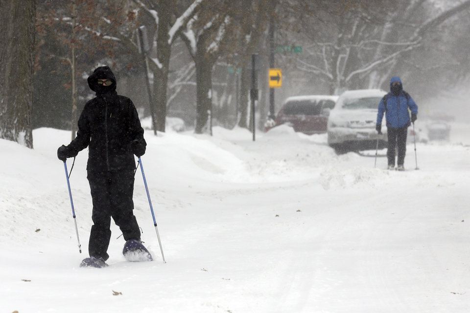 Photo - People ski on the street in Evanston, Ill., on Sunday, Jan. 5, 2014. Sunday night temperatures will drastically drop to about minus 20 degrees. (AP Photo/Nam Y. Huh)