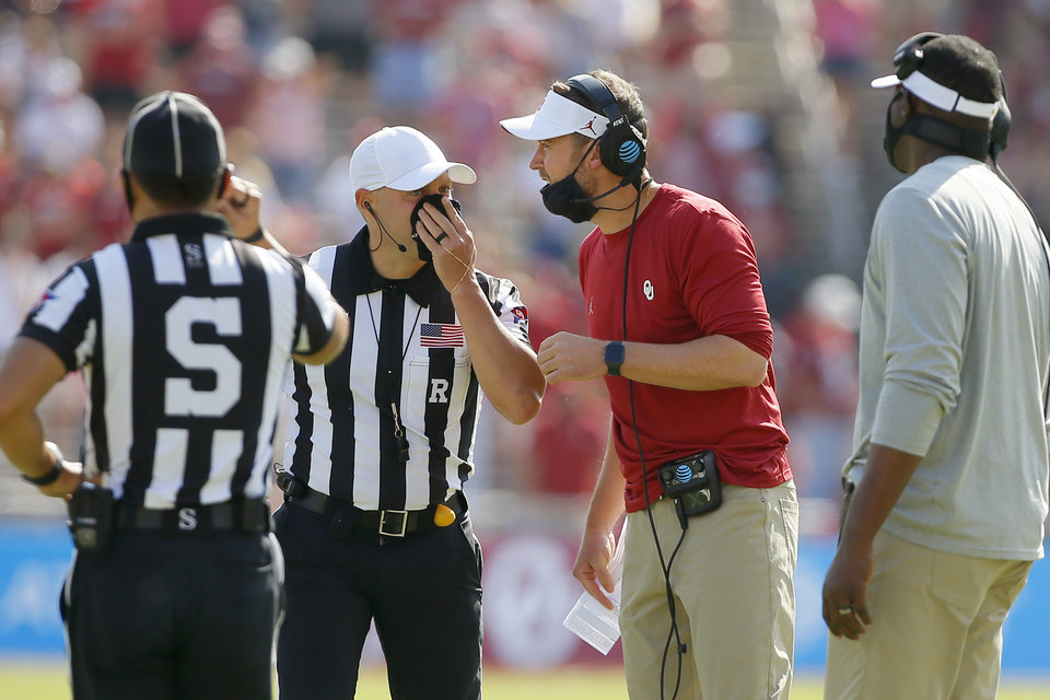 Photo - Oklahoma coach Lincoln Riley talks with an official during the Red River Showdown between OU and Texas at the Cotton Bowl in Dallas on Saturday. Monday, the Big 12 acknowledged a clock error in the fourth quarter that extended the game. [Bryan Terry/The Oklahoman]