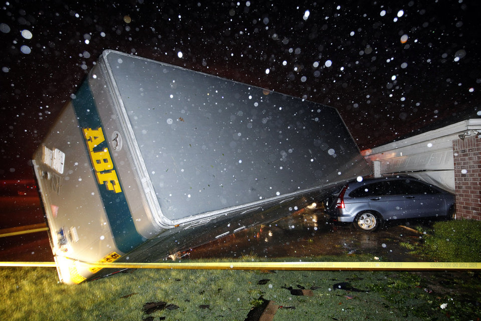 A trucking company trailer landed on a car that was parked in front of a Lindsey Ln. home in Cleburne Texas after a powerful storm went through Wednesday night, May 15, 2013. Neighbors say the trailer was parked on the street and was rolled over onto the car. (AP Photo/The Dallas Morning News, Tom Fox)
