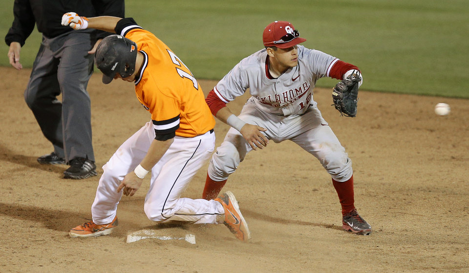 Photo - OSU's Gage Green makes it to second as OU's Hector Lorenzana waits for the ball in the 15th inning of a Bedlam baseball game between Oklahoma State University and the University of Oklahoma in Stillwater, Tuesday, April 15, 2014. Photo by Bryan Terry, The Oklahoman