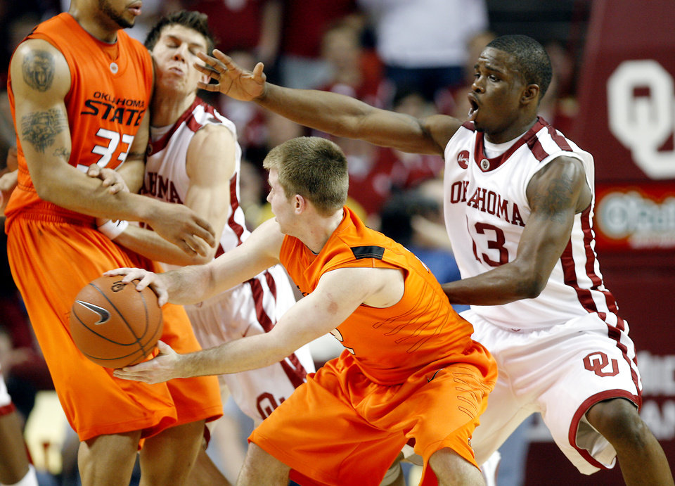 Photo - OU's Willie Warren (13) defends on OSU's Keiton Page (12) during the second half of the college bedlam basketball game between The University of Oklahoma Sooners (OU) and Oklahoma State University University Cowboys (OSU) at the Lloyd Noble Center on Monday, Jan. 11, 2010, in Norman, Okla.