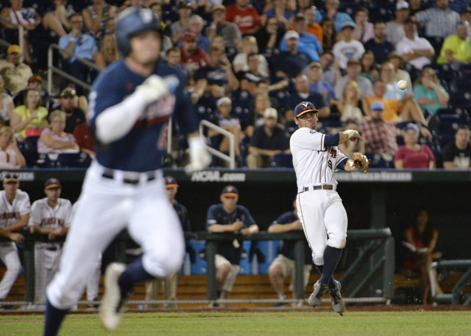 Photo - Virginia third baseman Kenny Towns (9) handles a ground ball as Vanderbilt right fielder Rhett Wiseman runs safely to first base in the seventh inning of game one of the best-of-three NCAA baseball College World Series finals in Omaha, Neb., Monday, June 23, 2014. (AP Photo/Ted Kirk)