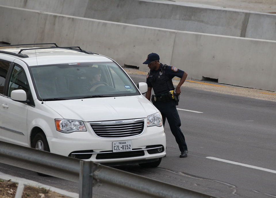 Photo - A police officer checks drivers' IDs outside the main gate at Fort Hood, Texas, after a shooting at the Army base Wednesday, April 2, 2014.  One person was killed and at least 14 injured in a shooting Wednesday at Fort Hood. (AP Photo/Austin American-Statesman, Deborah Cannon)  AUSTIN CHRONICLE OUT, COMMUNITY IMPACT OUT, MAGS OUT; NO SALES; INTERNET AND TV MUST CREDIT PHOTOGRAPHER AND STATESMAN.COM