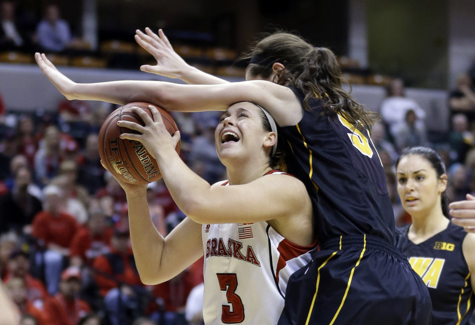 Photo - Iowa center Bethany Doolittle, right, fouls Nebraska forward Hailie Sample in the second half of an NCAA college basketball game in the finals of the Big Ten women's tournament in Indianapolis, Sunday, March 9, 2014. Nebraska defeated Iowa 72-65. (AP Photo/Michael Conroy)