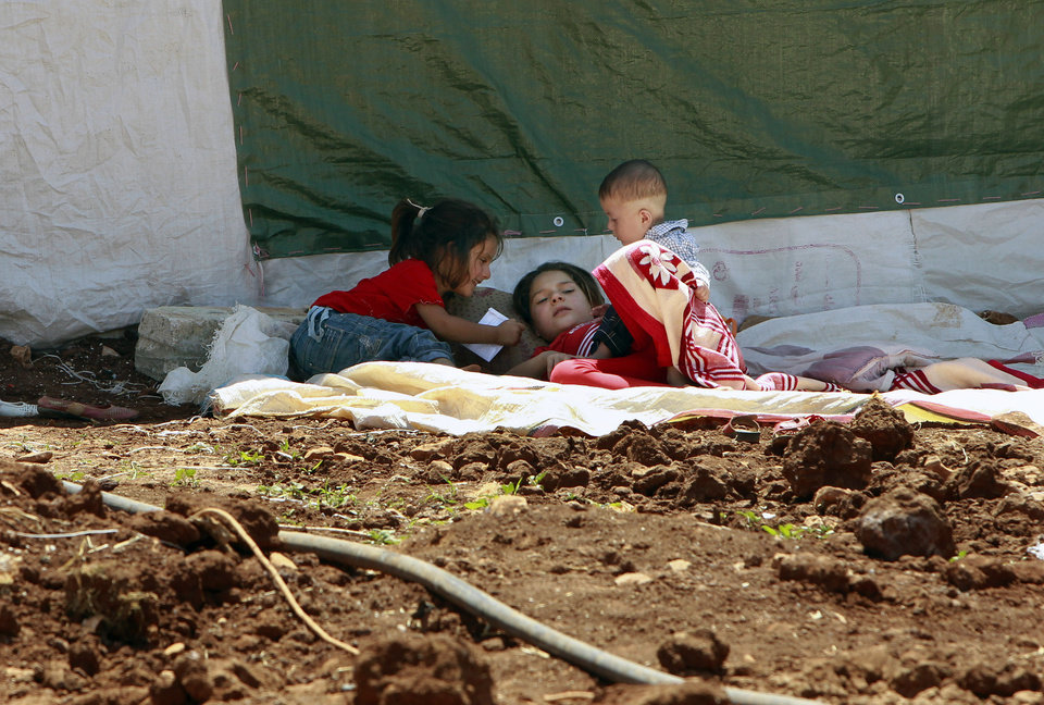 Photo - Syrian refugees children sleep outside their tent, at a temporary refugee camp in the eastern Lebanese town of Faour near the border with Syria, Lebanon, Wednesday, Aug. 28, 2013. U.N. chemical weapons experts headed to a Damascus suburb on Wednesday for a new tour of areas struck by a purported poison gas attack, activists said, as the U.S. laid the groundwork for a possible punitive strike and the U.N. chief pleaded for more time for diplomacy. (AP Photo/Bilal Hussein)