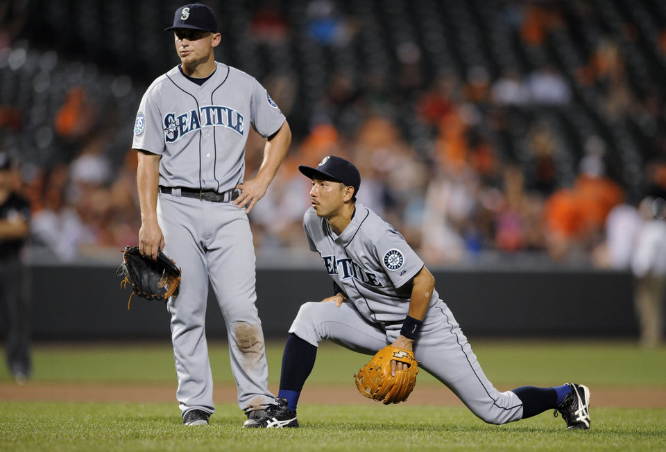 Photo -   Seattle Mariners third baseman Kyle Seager, left, and shortstop Munenori Kawasaki, of Japan, right, wait during a pitching change during the seventh inning of a baseball game against the Baltimore Orioles, Wednesday, Aug. 8, 2012, in Baltimore. The Orioles won 9-2. (AP Photo/Nick Wass)