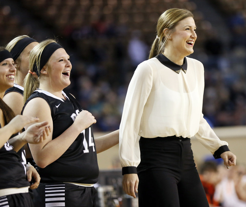 Photo - Pond Creek-Hunter coach Tasha Diesselhorst smiles next to Jaicee Stinson (14) and other members of her team near the end of a Class A girls semifinal high school basketball game in the state championship tournament between Pond Creek-Hunter and Cheyenne/Reydon at The Big House, Jim Norick State Fair Arena, in Oklahoma City, Friday, March 7, 2014. Photo by Nate Billings, The Oklahoman