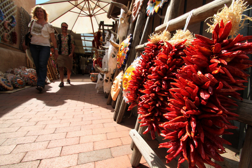 Photo - This July 14, 2010 image shows tourists approaching a display of chile ristras at one of the shops near the historic plaza in Santa Fe, N.M. A national historic landmark, the plaza has served as the commercial, social and political center of Santa Fe since the early 1600s. It plays host to art markets through the year and is home to the Palace of the Governors, the nation's oldest continuously occupied public building. (AP Photo/Susan Montoya Bryan).