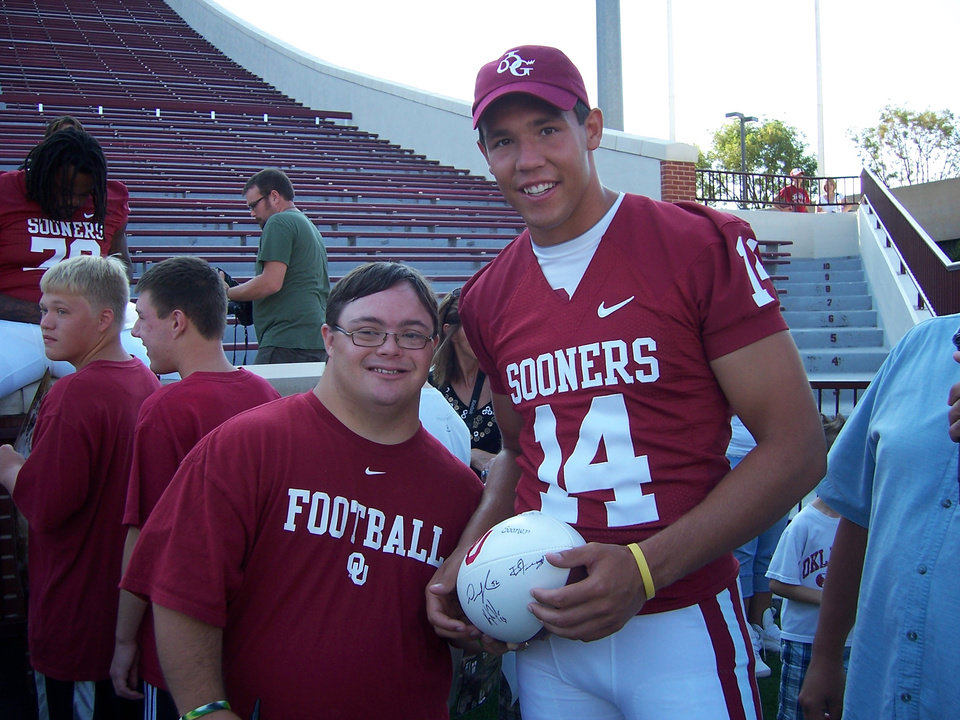 Photo - Photo by reader BJ Cowden. University of Oklahoma quarterback Sam Bradford wearing my Cherokee OU cap. He put it on for me and posed with my nephew, Michael Arnold (also Cherokee), during the OU Special Olympic/Media/Fan Day (August '08). I ordered quite a few of the caps from the Cherokee Nation and have given them to family members, friends, and others. When I ordered the caps, I told them about the picture of Sam wearing my cap and they were thrilled and wanted a picture; I just sent it to them tonight. They told me that the t-shirts were not available for purchase. I gave a cap to the Stoops (at a Christmas party for children with leukemia and cancer at Children's Hospital...my grandson, Garrett Hanska of Edmond is a leukemia survivor.) The thing that I think is so neat is the fact that so few people have seen anything with OU in Cherokee...that is, until tonight when the Cherokee Nation will give away t-shirts with the Cherokee OU. I sincerely doubt that there is another picture of Sam with a Cherokee identity of some sort.