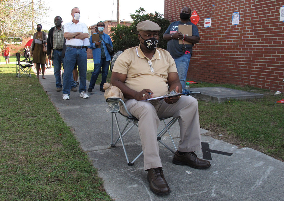 Photo -  Richard Williams sits in a folding chair, filling out paperwork, Wednesday as he waits in line to vote early in Savannah, Ga. [Russ Bynum/The Associated Press]
