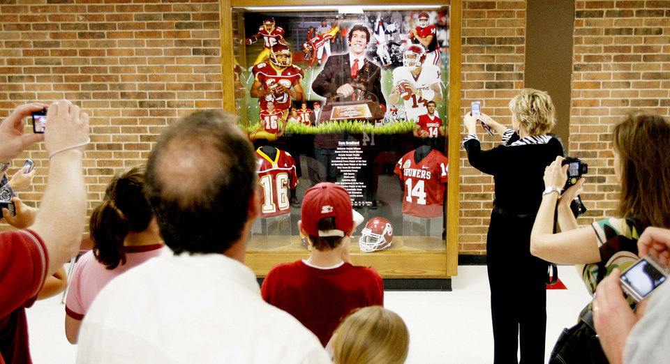 Photo - A crowd gathers around a trophy case honoring Sam Bradford after Friday's ceremony.  Photo by Bryan Terry, The Oklahoman