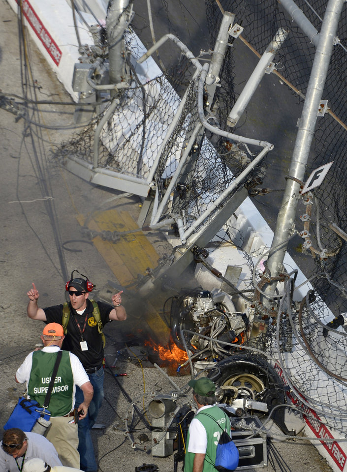 An emergency official ushers fans away from driver Kyle Larson's engine as it burns behind the wall and safety fence that he hit along the front grandstands on the final lap of the NASCAR Nationwide Series auto race at Daytona International Speedway in Daytona Beach, Fla., Saturday, Feb. 23, 2013. (AP Photo/Phelan M. Ebenhack)