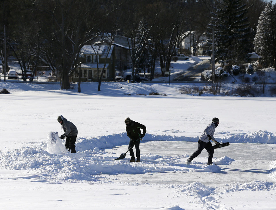 Photo - Alex Herrick, Adam Scirico and Peter Herrick clear a section of Hampton Manor Lake to play ice hockey on Friday, Jan. 3, 2014, in East Greenbush, N.Y. Upstate New York on Friday had temperatures in the single digits with below-zero wind chills. (AP Photo/Mike Groll)