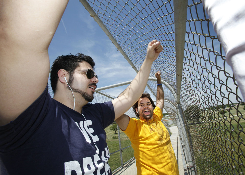 Fredy Valencia and Amir Darvishzadeh hold their hand up in a fist to show solidarity while protesting on the walk bridge over Interstate 44 in Woodson Park. The rally was a part of a national campaign to raise awarness about the Dream Act. David McDaniel - The Oklahoman