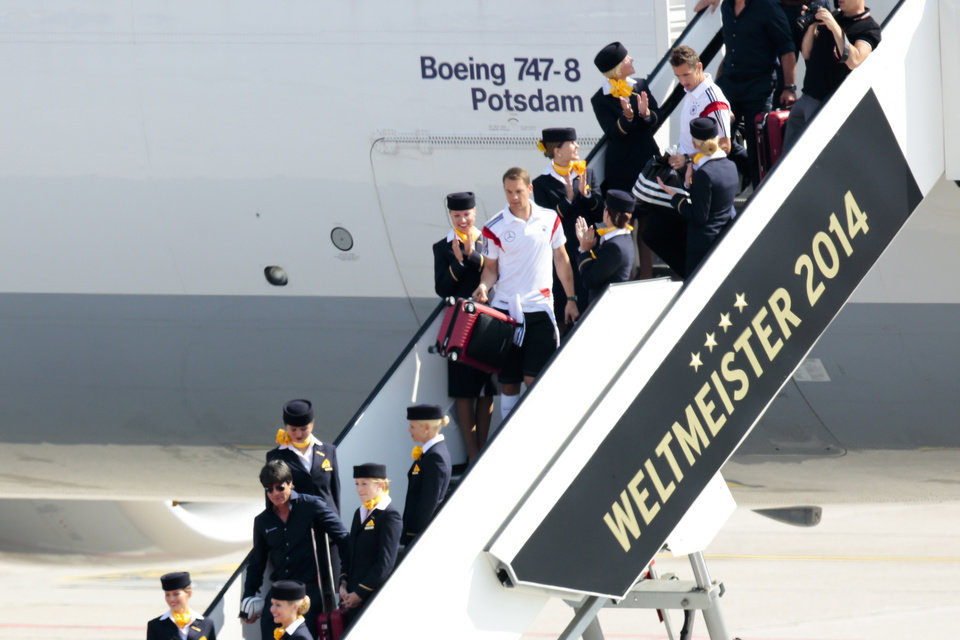 """Photo - The coach of German national soccer team Joachim Loew, 2, from left, goalie Manuel Neuer, center, and player Miroslav Klose arrive at  Tegel airport  in Berlin Tuesday, July 15, 2014.   Germany's World Cup-winning team has returned home  from Brazil to celebrate the country's fourth title with huge crowds of fans. The team's Boeing 747 touched down at Berlin's Tegel airport midmorning Tuesday after flying a lap of honor over the """"fan mile"""" in front of the landmark Brandenburg Gate. Words read: World Champion 2014.  (AP Photo/Markus Schreiber)"""