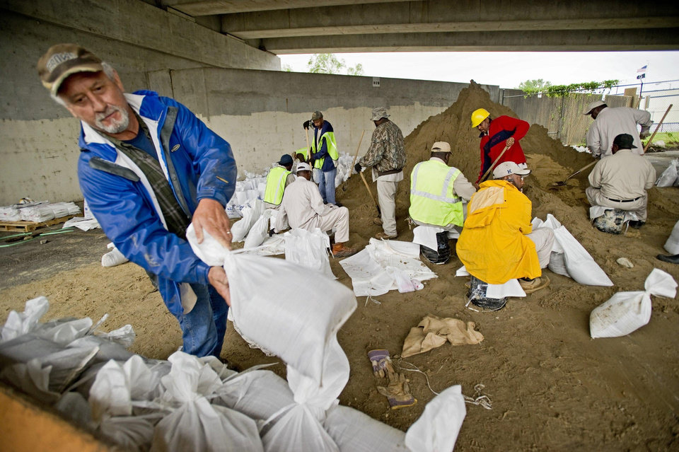 Photo - Working under the Auction Ave. bridge in Downtown, Memphis, Tenn., Memphis Public Works employees, including Dennis Ramsey, left, fill sand bags for use in areas with a high risk of flooding as a series of strong storms continues to raise water levels along the Mississippi River to near-record highs Wednesday, April 27, 2011. (AP Photo/The Commercial Appeal, Brandon Dill)