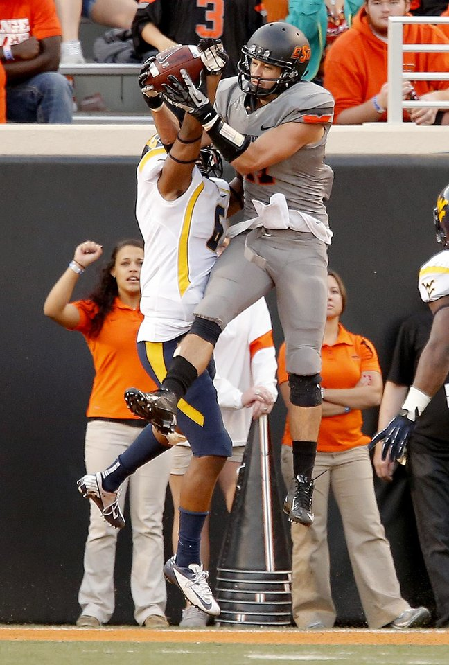 Photo - Oklahoma State's Charlie Moore (17)  catches a touchdown in the third quarter during a college football game between Oklahoma State University (OSU) and the West Virginia University at Boone Pickens Stadium in Stillwater, Okla., Saturday, Nov. 10, 2012. Photo by Sarah Phipps, The Oklahoman