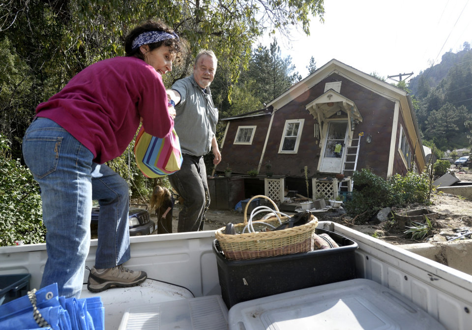 Photo - Shireen Malik,  left, and Bruce Orr help salvage belongings out of the home of Kathleen McLellan in Salina, Colo., on Thursday, Sept. 19, 2013, in Boulder County.   Residents displaced by last week's flooding in the Colorado returned Thursday to salvage what they could from their homes.  (AP Photo/The Daily Camera, Jeremy Papasso) NO SALES