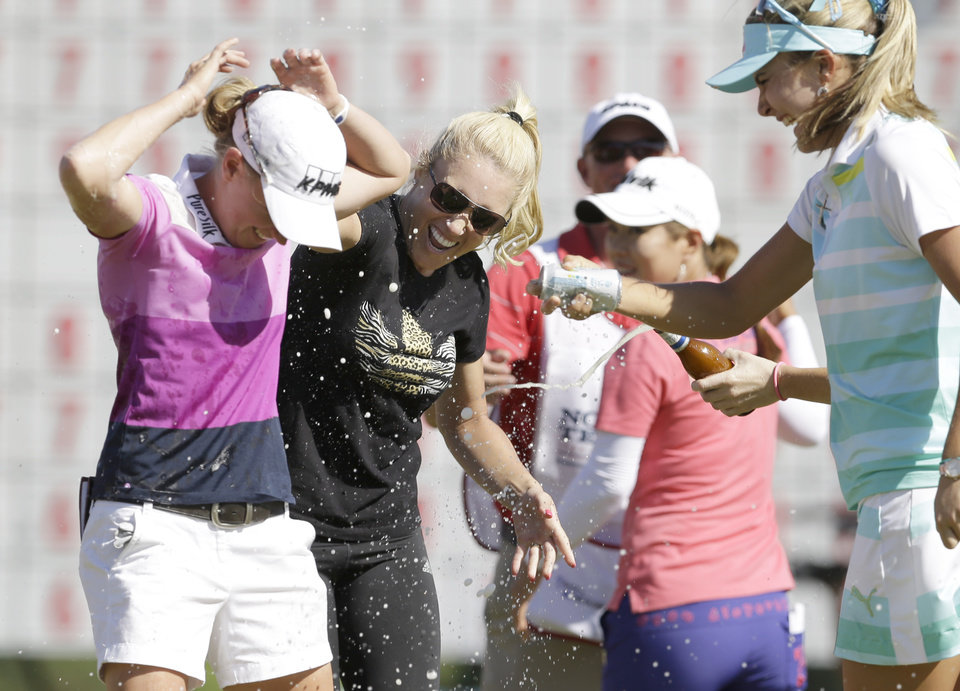 Photo - Stacy Lewis, left, is sprayed by Lexi Thompson, right, and Natalie Gulbis after winning the North Texas LPGA Shootout golf tournament at Las Colinas Country Club in Irving, Texas, Sunday, May 4, 2014. (AP Photo/LM Otero)