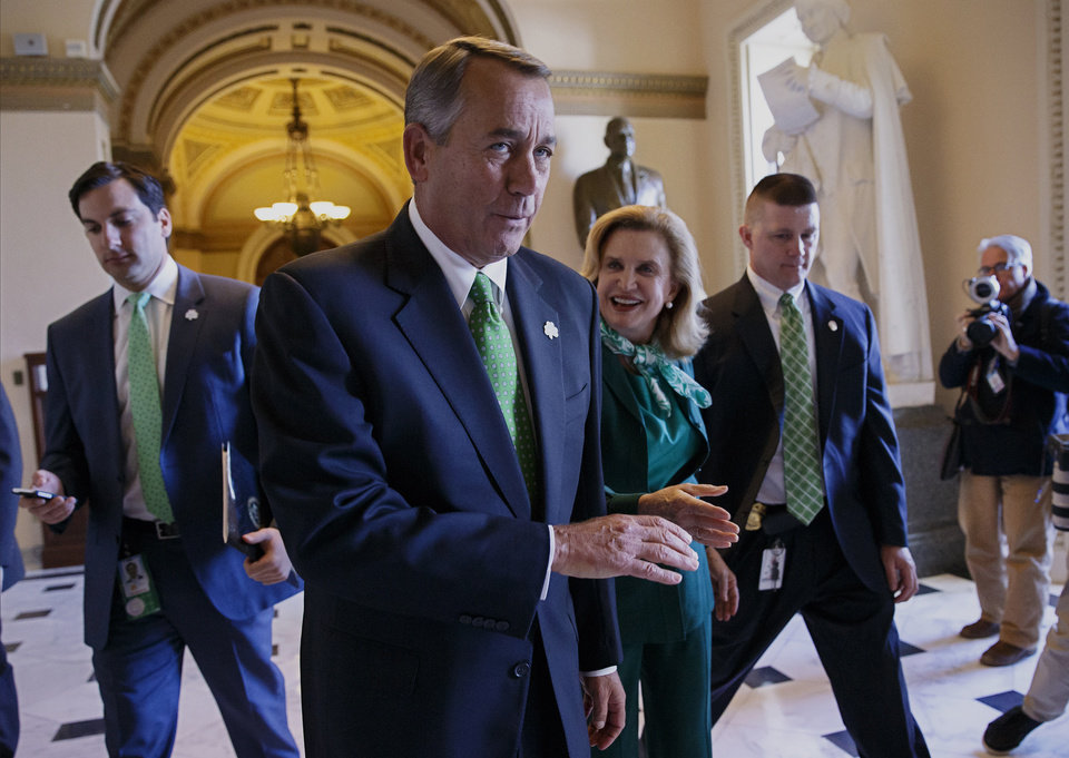 Photo - After being greeted by Rep. Carolyn Maloney, D-NY, center right, House Speaker John Boehner of Ohio leaves the House chamber on Capitol Hill in Washington, Friday, March 14, 2014, where the Republican-controlled House voted for the 51st time in 26 months to neuter the nation's health care law. With the vote 238-181 and nearly all Democrats opposed, the bill now goes to the Senate, where it's expected to die. The measure would overhaul the system for paying doctors and others who treat Medicare patients. At the same time, it delays the penalty for failing to purchase coverage under the law.  (AP Photo/J. Scott Applewhite)