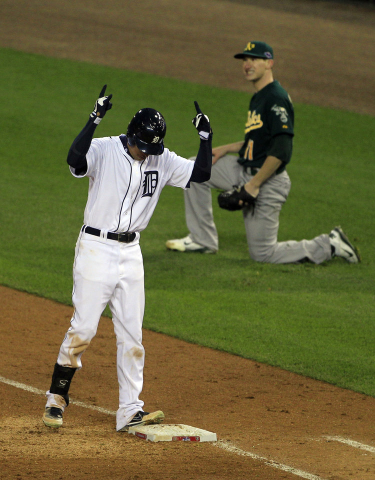 Photo -   Detroit Tigers Quintin Berry reacts after safely reaching first base as Oakland Athletics starting pitcher Jarrod Parker, background, looks on during the third inning of Game 1 of the American League division baseball series, Saturday, Oct. 6, 2012, in Detroit. The Tigers' Omar Infante scored and Parker was charged with a fielding error on the play.(AP Photo/Carlos Osorio)