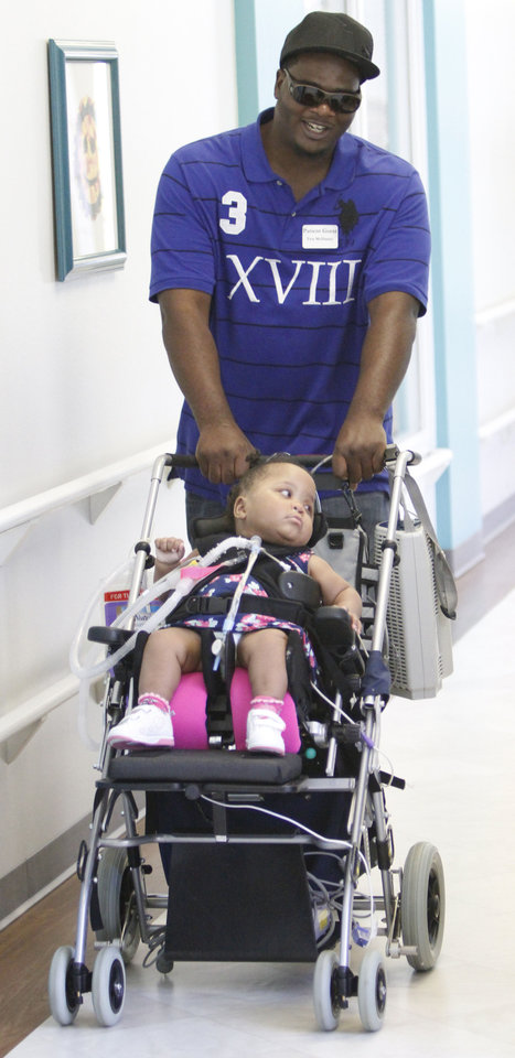 Photo - 21 month old Taliya McDaniel, is pushed by her father Tom McDaniel at the Children's Center in Oklahoma City, Thursday August 9, 2012. The center is holding Olympic games for the children at the center. Photo By Steve Gooch, The Oklahoman  Steve Gooch - The Oklahoman