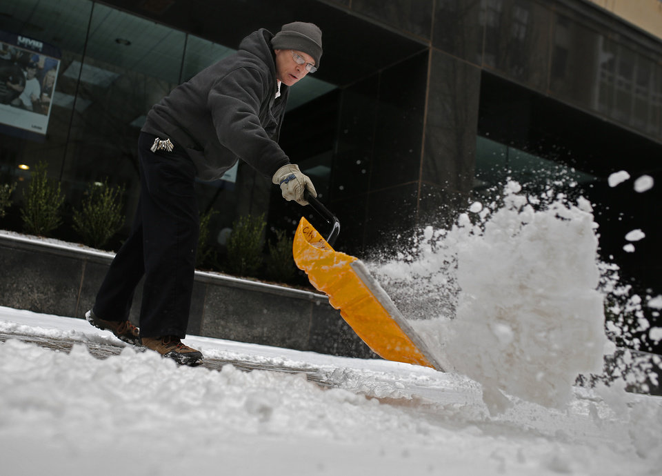Photo - Mike Strawn with City Place Office building shovels snow on a sidewalk in downtown Oklahoma City following a winter storm that moved through the area Sunday, Feb. 2, 2014.  Photo by Sarah Phipps, The Oklahoman