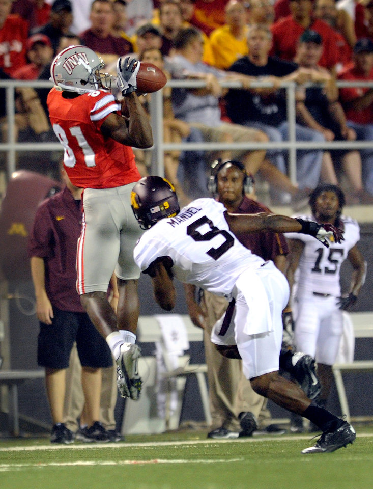 Photo -   UNLV's Devante Davis, left, makes a reception with Minnesota's Philip Nelson (9) covering during their NCAA college football game, Thursday, Aug. 30, 2012, in Las Vegas. (AP Photo/David Becker)