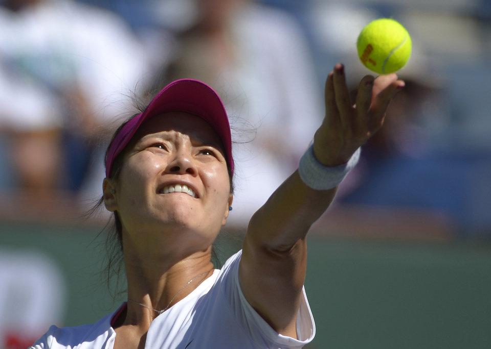 Photo - Li Na, of China, serves to Zheng Jie, of China, during their match at the BNP Paribas Open tennis tournament, Saturday, March 8, 2014, in Indian Wells, Calif. (AP Photo/Mark J. Terrill)